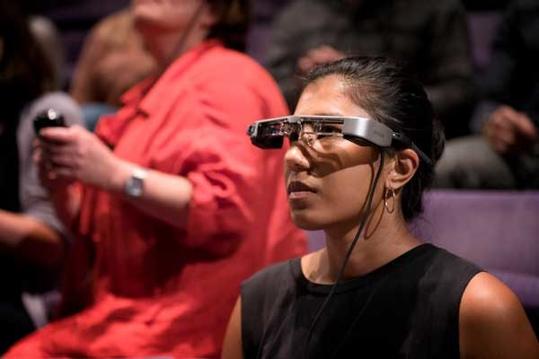 A photograph of a women wearing smart glasses