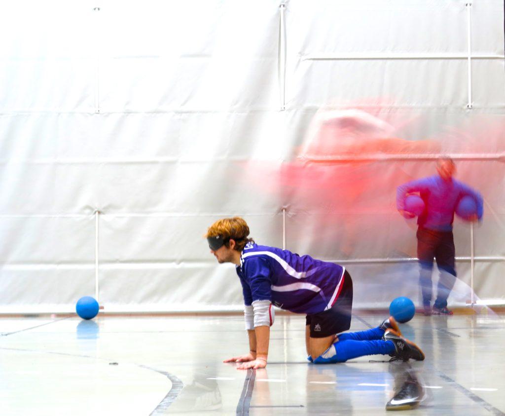 Blindfolded man kneeling on a sports court