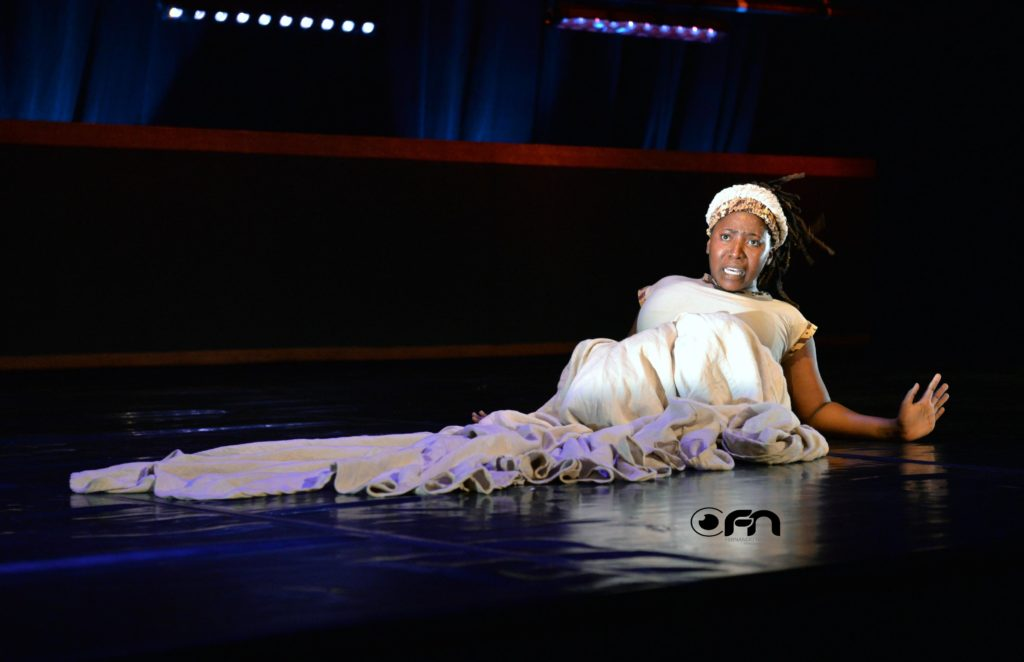 Woman lying on stage looking shocked