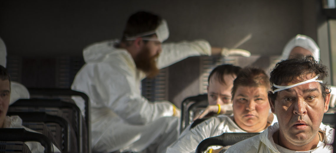 Six people are sitting on a bus wearing white overalls