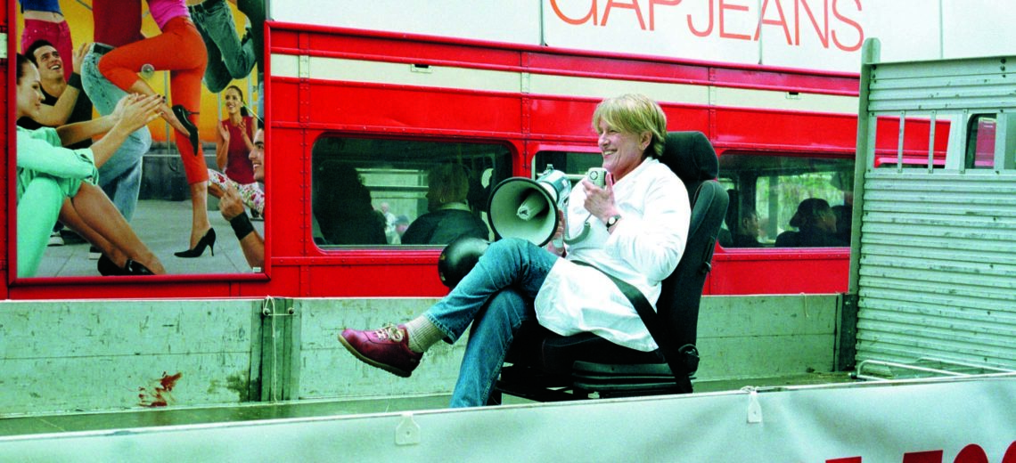 Woman sat on a chair with a megaphone in front of a bus