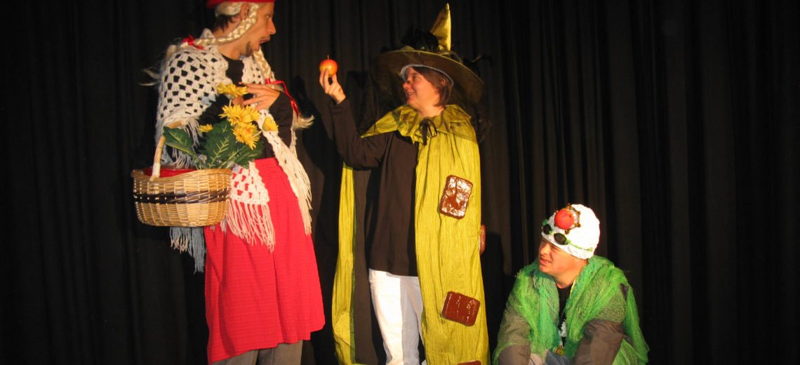 Three performers on a stage, each dressed in a fancy dress outfit.