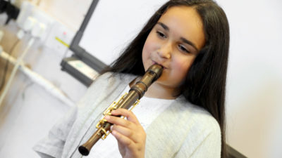 A girl playing a one-handed Recorder