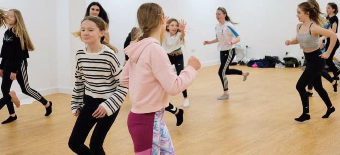Youth dancers smiling and travelling around community dance space