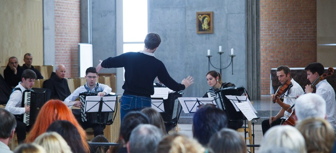 A man conducting a small orchestra in front of an audience.