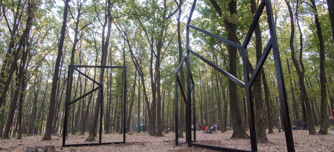 Three large square steel structures erected amidst tall trees.