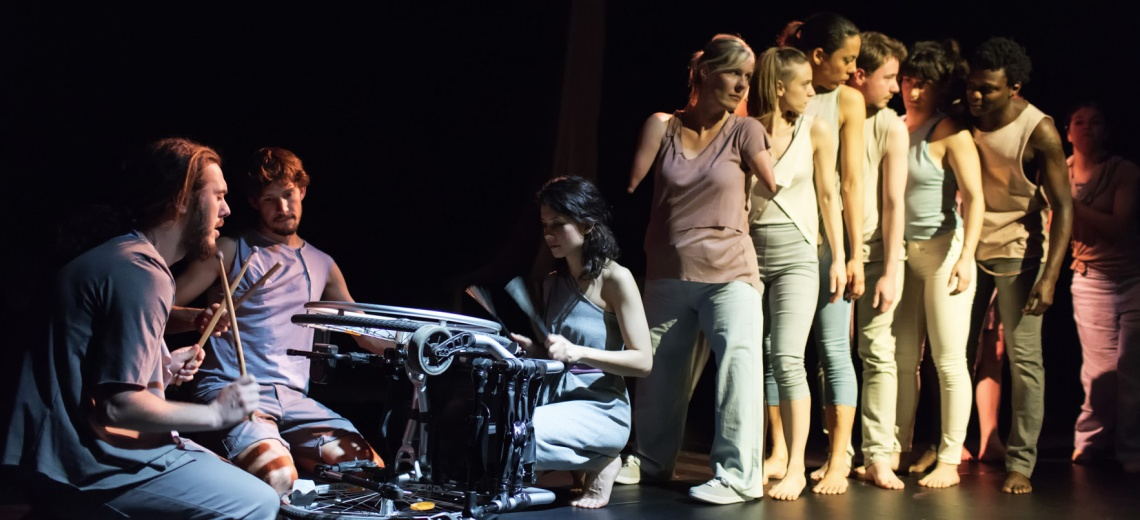 Performers stand in a line behind an overturned wheelchair