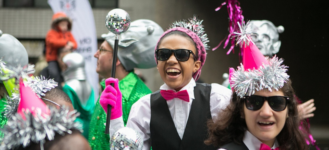 A group of performers outdoors, wearing tinsel covered party hats.