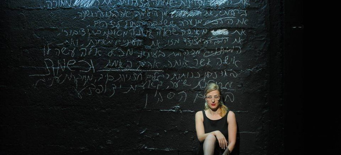 A performer sitting in front of a black wall covered in white chalk writing.