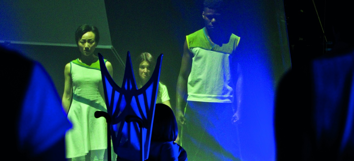 three performers with blue light cast onto them