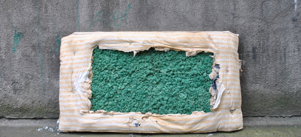 A mattress propped up against a wall. The middle of the mattress is filled with green stones.