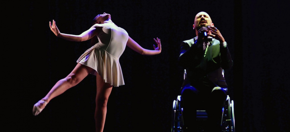 A man in a wheelchair holding a microphone and a woman in a ballet pose.