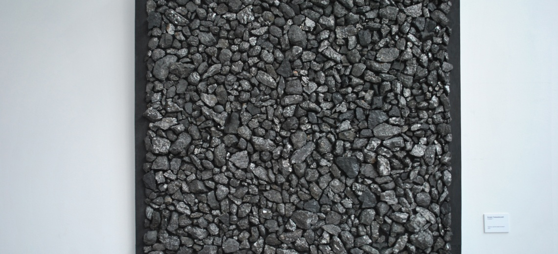 A collection of grey stones packed into in a square frame, hung on a wall.