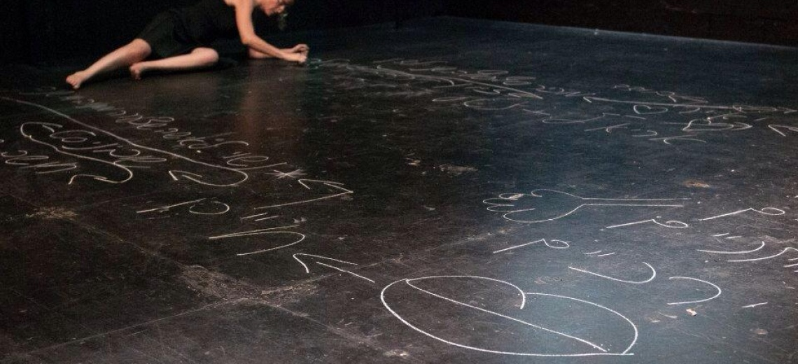 A performer lying on a black stage floor which is covered in chalk writing and pictures.
