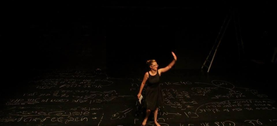 A performer standing waving on a black stage floor which is covered in chalk writing and pictures.