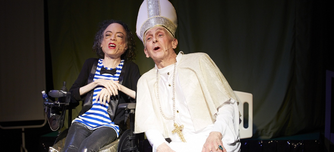 A woman in a power assisted chair next to a man dressed as a bishop.
