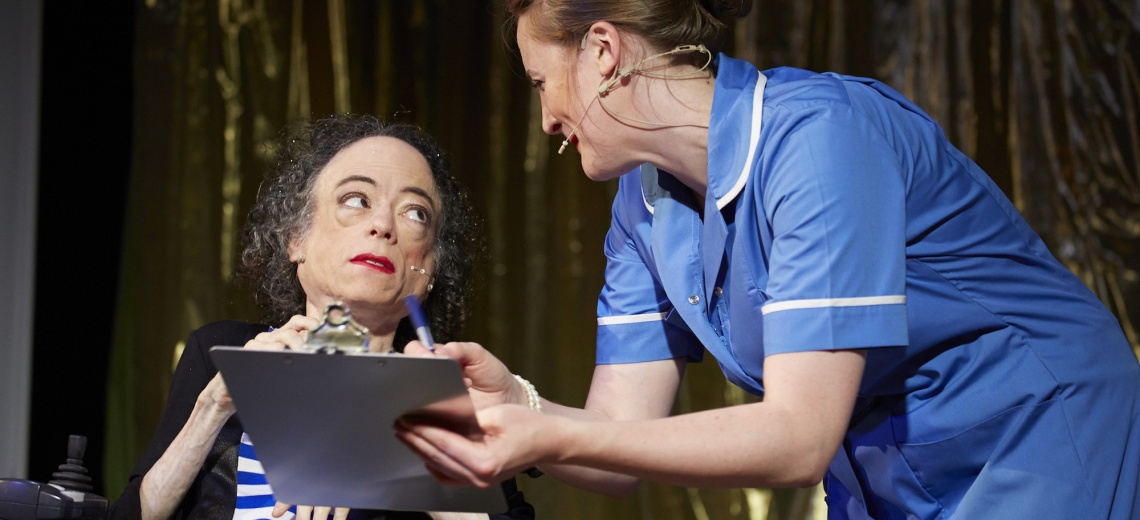 Two performers on a stage, one is dressed as a nurse.
