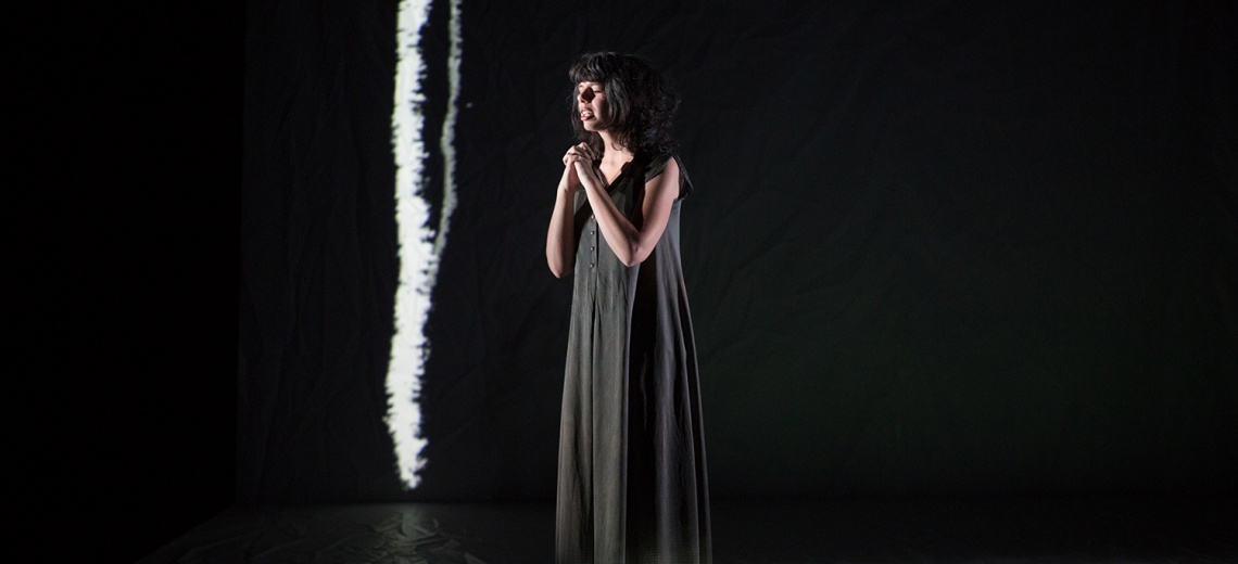 A performer on a dark stage with her hands clasped at her chest.