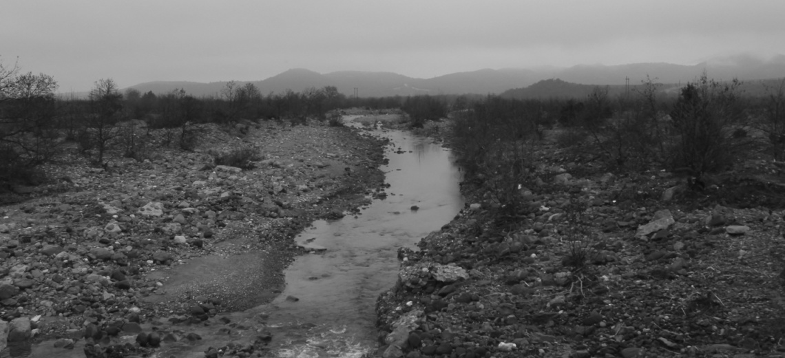 A stream running through a barren and rocky landscape with sparse vegetation.