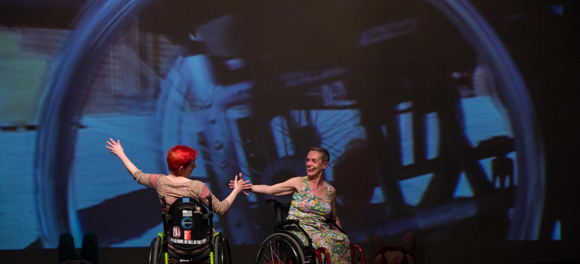 Two women in wheelchairs on stage.