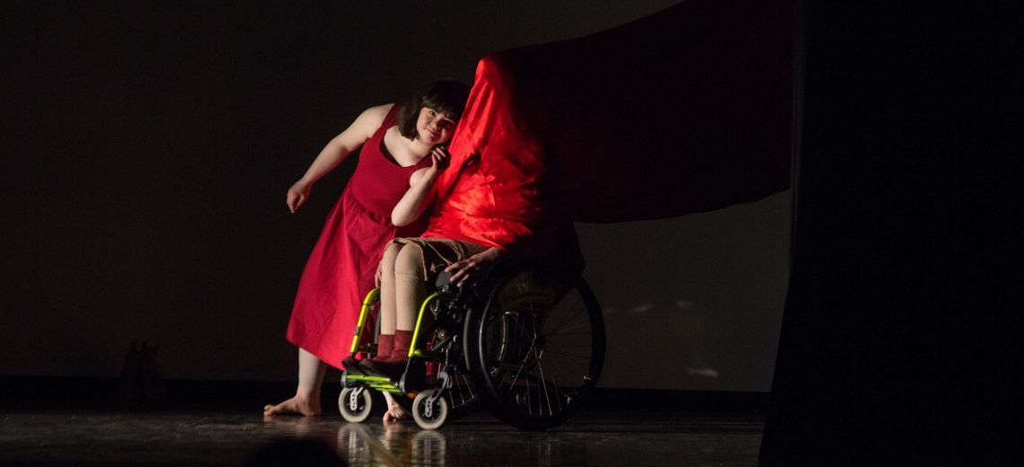 Two people on a dark stage. One is in a wheelchair with a red cloth draped over their head and body.
