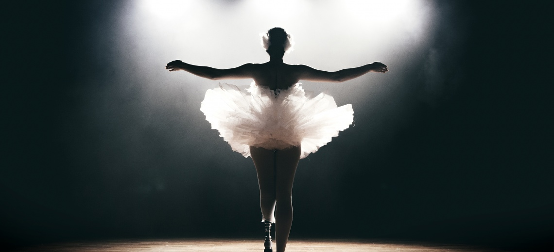 The back of a dancer with a prosthetic lower left limb, standing with arms outstretched in a ballet pose.