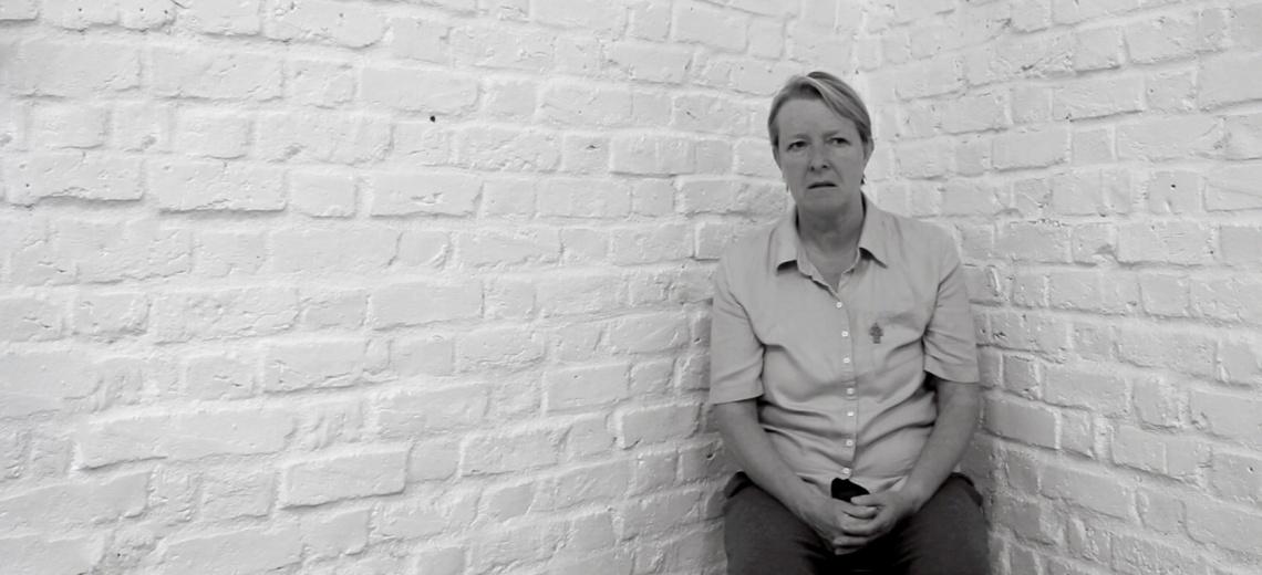 Woman sat against a white brick wall