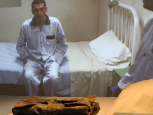 Two men wearing pyjamas, one of whom is sitting on the edge of a white metal framed bed, the other is in partial shot, in the foreground of the photograph.