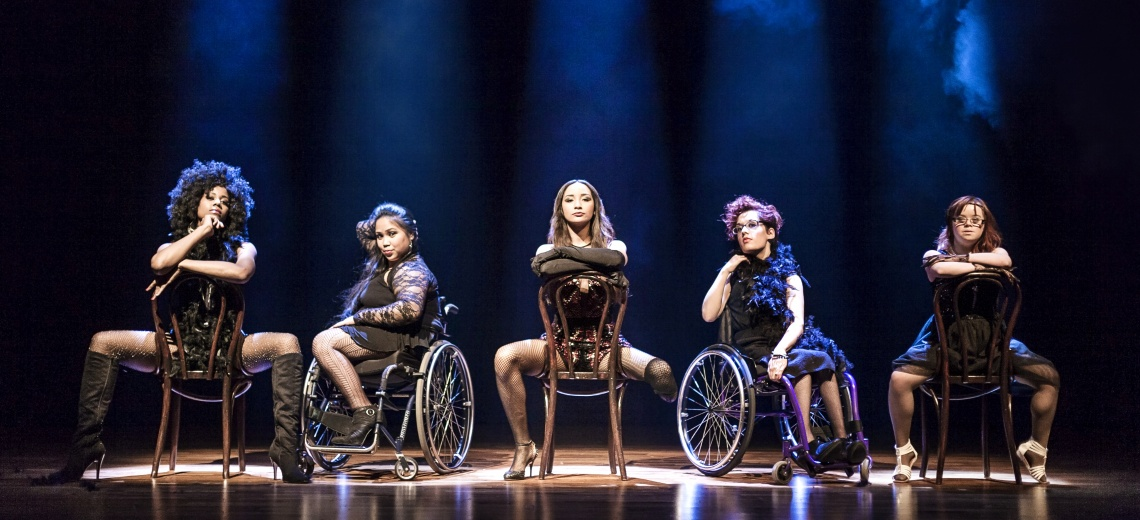 Five female performers on a stage, three are straddled across the back of their chairs, two are using wheelchairs.