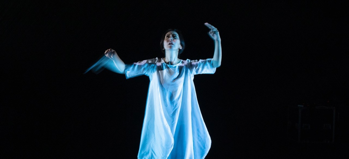 A woman on a dark stage looking upwards and with raised arms.