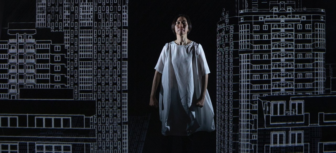 A woman stood on stage between two line drawings of high rise buildings.