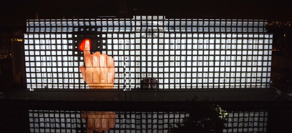 A light projection onto a building of a large hand pressing a red switch.