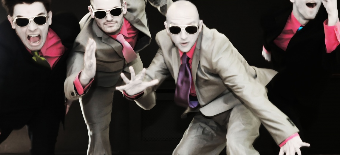 Four performers posing on stage, wearing suits and dark glasses
