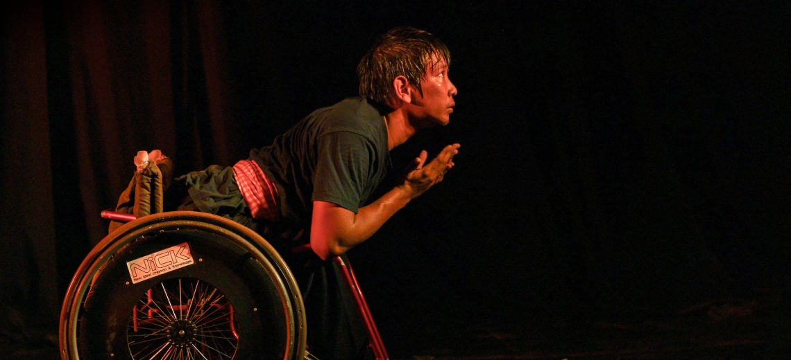 A performer in a wheelchair on a dark stage.