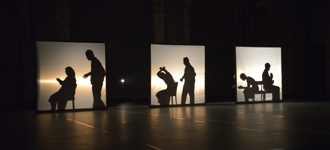 A silhouette of six performers behind back lit screens.