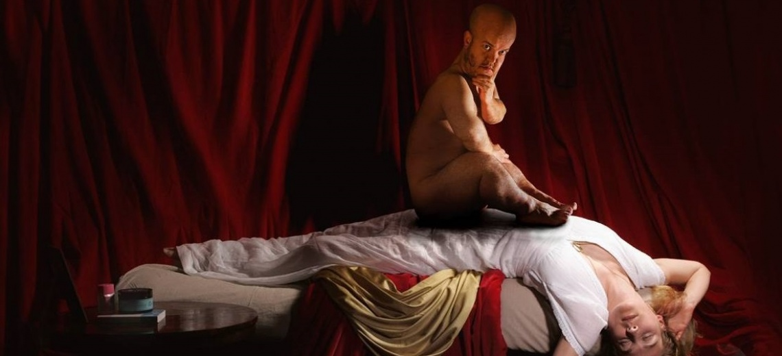 Man of short stature sitting on a woman who is lying over a bed.