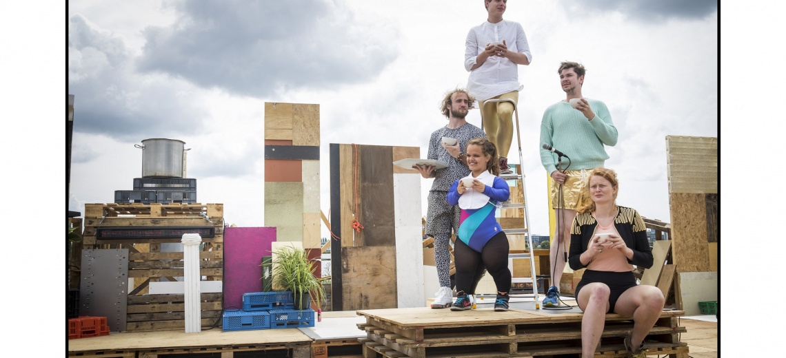 5 performers sitting on a stack of pallets