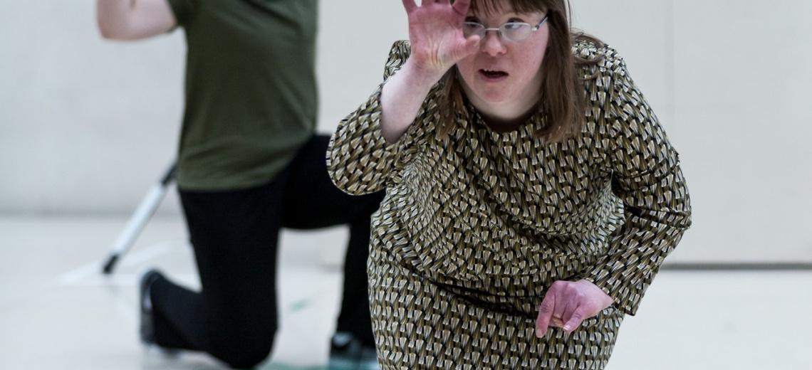 A woman facing the camera, bending forward, raising her hand.