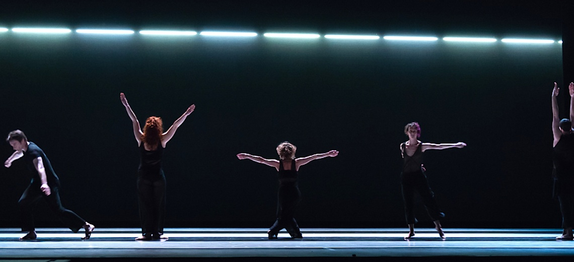 Five dancers on a dark stage in different poses with outstretched arms.
