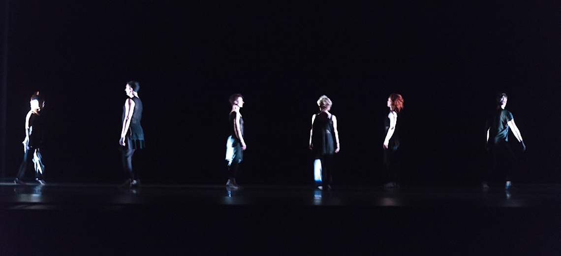 Six dancers at a distance, on a stage.