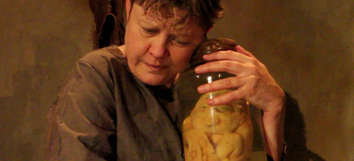 Woman hugs a jar which seems to contain body parts