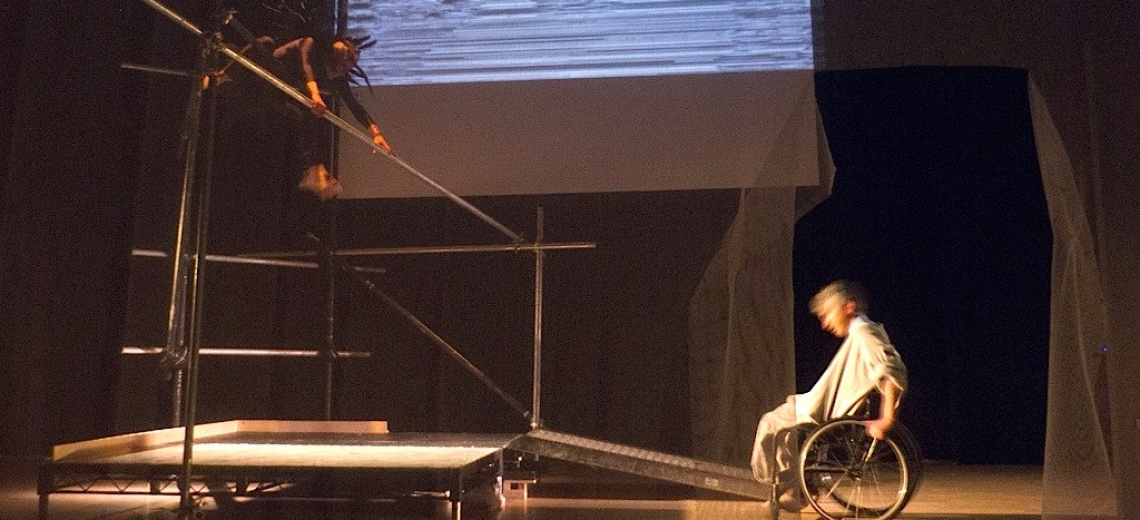 Two performers on a stage. One is on a scaffold platform, and the other is in a wheelchair at the bottom of a ramp.
