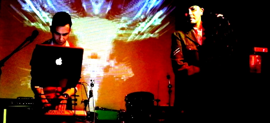Two men on a stage with a projection as a backdrop.