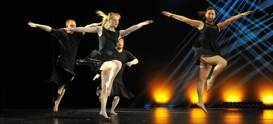 Four dancers on a stage with arms outstretched and right legs bent in the air.
