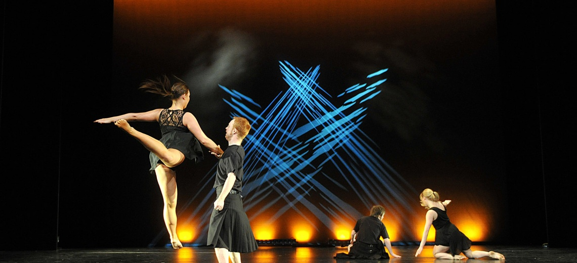 Four dancers; two male and two female, on a stage dark stage.