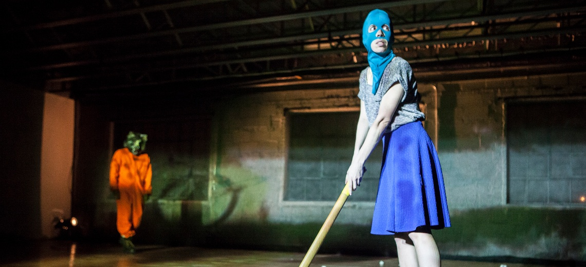 Two performers one wearing a blue full balaclava, and the other wearing a wolf's head.