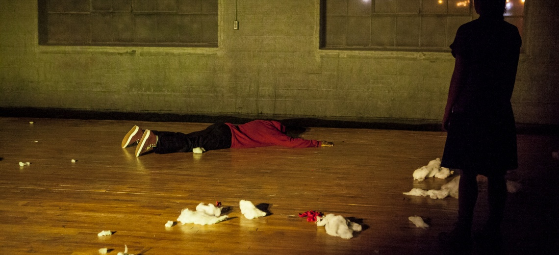 Two performers, one lying face down on the ground.