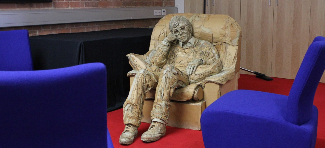 A sculpture of a man sitting in an armchair.