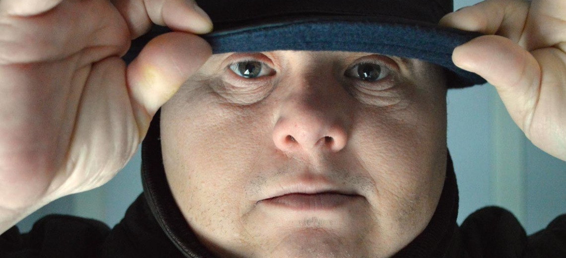 A close up shot of a man's face holding the peak of his cap.