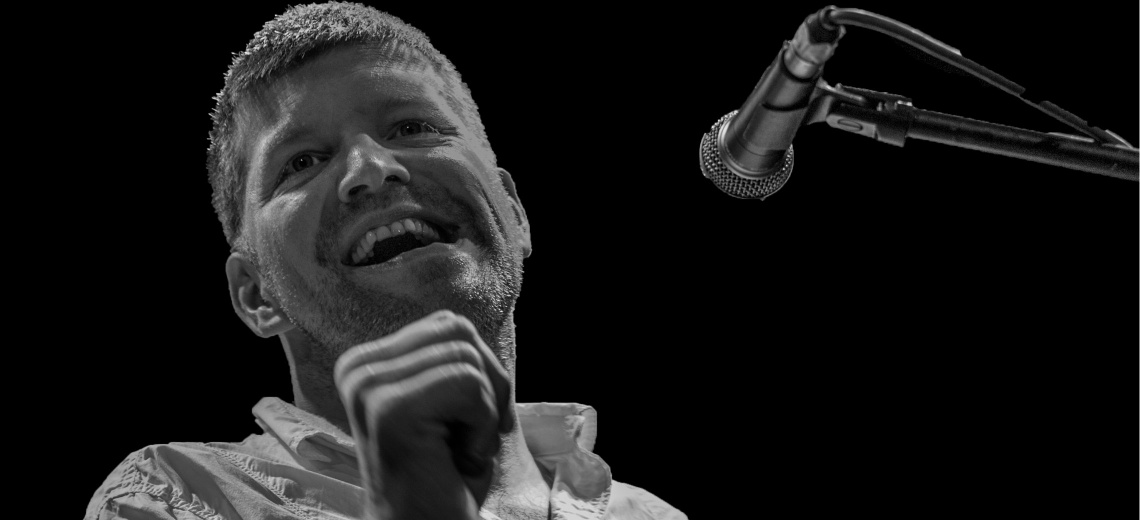A  male performer laughing, next to a microphone on a stand.